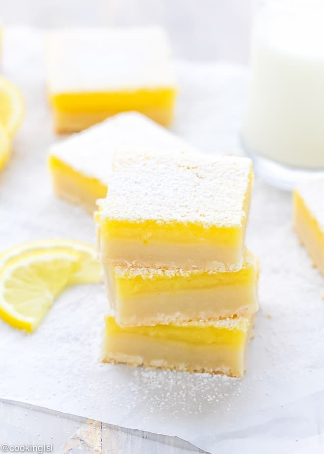 Thick and tangy classic lemon bars, perfectly cut on top of each other, dusted with powder sugar