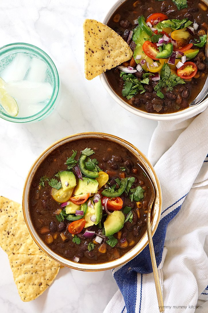This slow cooker black bean soup is made from scratch with dried black beans, veggies, and spices. Load it up with toppings for a delicious vegetarian and vegan soup!