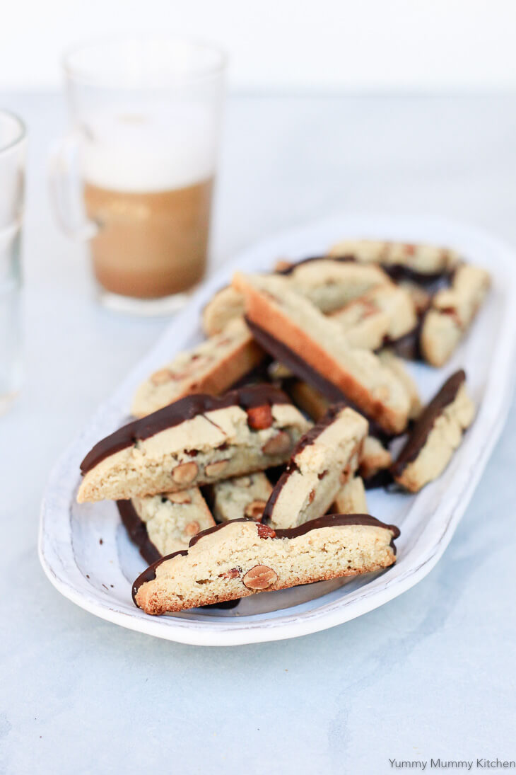 A plate of almond biscotti dipped into chocolate. These healthier biscotti or cantucci are made with almond flour and are gluten free and vegan.