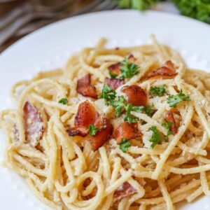 Spaghetti Carbonara topped with bacon and parsely on a white plate